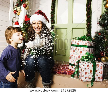 happy family on Christmas in red hats waiting gests and smiling outdoor gifts