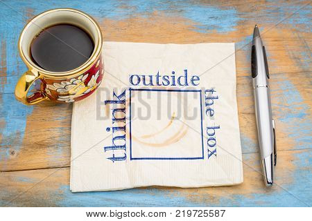 Think outside the box concept - hadwiting on a napkin with a cup of coffee