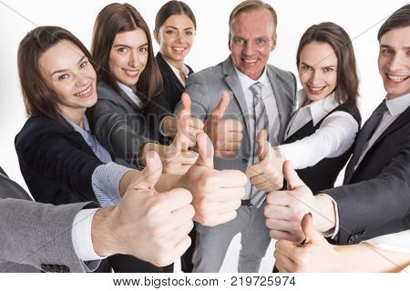 Cheering business people holding many thumbs thumbs up closeup