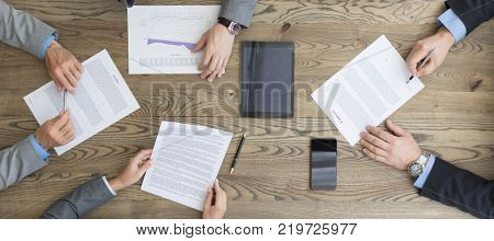 Business people discuss contract sitting around office table, top view