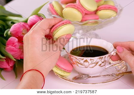 Woman's hands holding pink macaroon or macaron dessert . Energy load at morning. macaroons cakes and cup of espresso coffee
