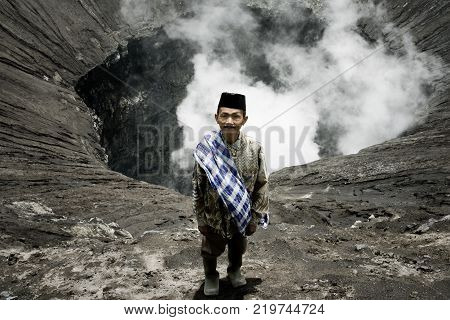 Tenggerese man standing on the edge of an active volcano in Bromo Tengger Semeru National Park. January 17 2014 - Java Indonesia