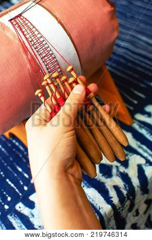 Making bobbin lace in traditional way. Detail on hands holding wooden bobbins with wound thread. Pillow lace.