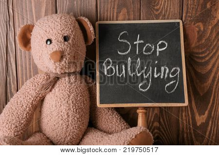 Chalkboard with text STOP BULLYING and toy on wooden background