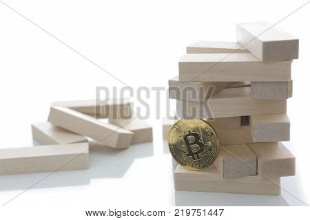 The bitcoin coin holds a game of wooden bricks embodying the basis of all the currency and exchange rate