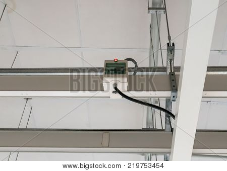 electrical panel controls and switches in the box hanging on the metal bar on the ceiling