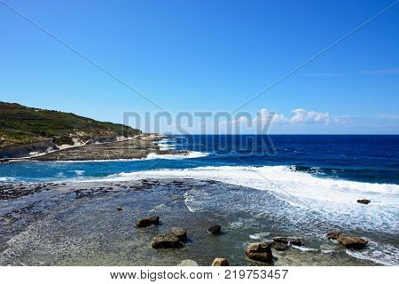 View along the coastline with rocks in shallow water in the foreground Redoubt Marsalforn Gozo Malta Europe.