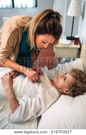Female caregiver auscultating senior woman at home