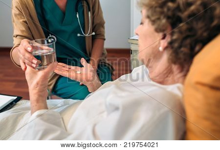 Female doctor giving medication dose to elderly patient