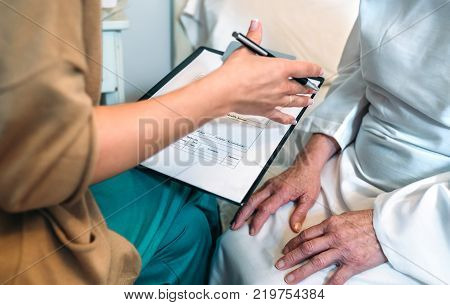 Female doctor filling out a questionnaire to a senior patient