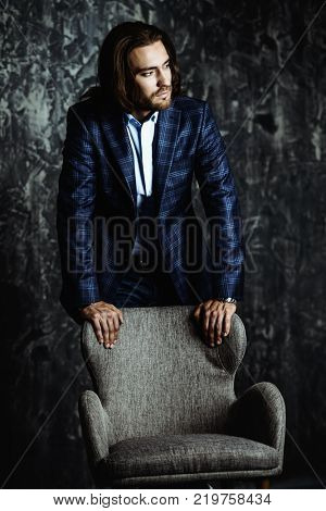 Imposing young man in elegant suit posing by the armchair at studio. Fashion. Business.