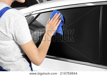 Female worker cleaning car window after applying tinting foil