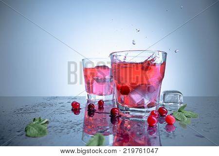 The closeup of a cape cod cocktail or vodka cranberry on blue studio background