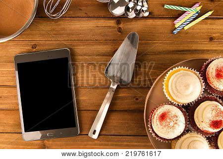 Cooking cupcake background with a digital tablet on wooden table. View from above.