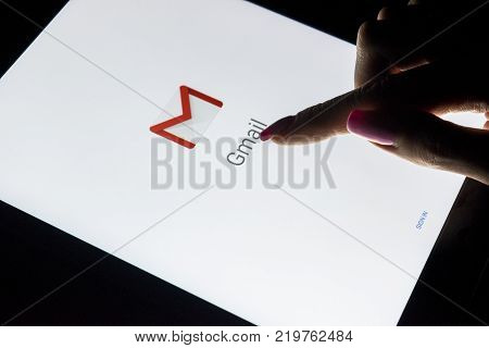 Sankt-Petersburg Russia December 21 2017: A woman's hand is touching screen on tablet computer iPad Pro at night with open Google Gmail application. Gmail is a free e-mail service provided by Google.