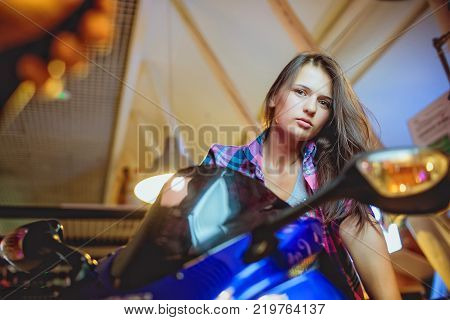 High angle view of sensual young brunette woman posing on motorcycle