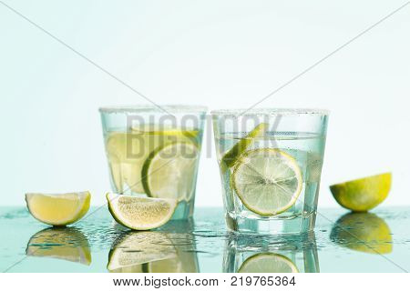 The closeup of a cape cod cocktail or vodka with fruits on blue studio background