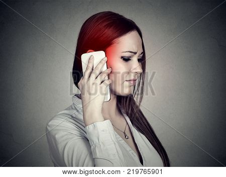 Upset unhappy woman talking on mobile phone isolated grey wall background. Cellular mobile radiation concept
