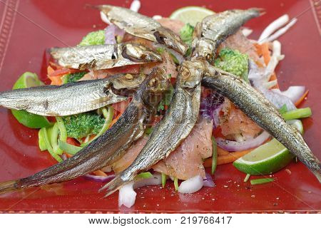smoked salmon and sprats with vegetables and lemon