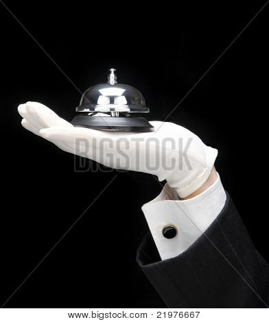 Butlers outstretched hand and arm with call bell