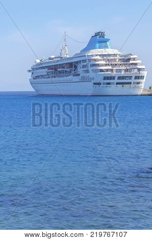 Big Modern Luxury Cruise Ship Docked At Marina Dock With Blue Sea Foreground