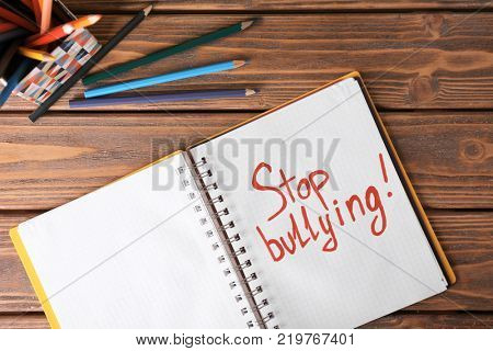 Notebook with text STOP BULLYING on wooden table
