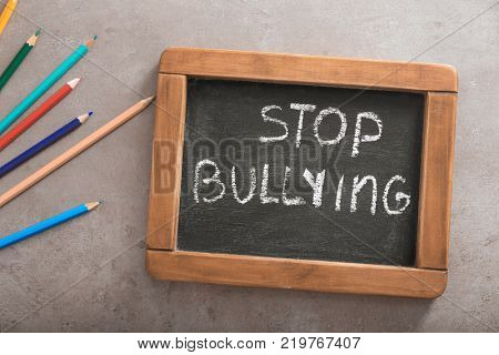 Chalkboard with text STOP BULLYING on grey background poster