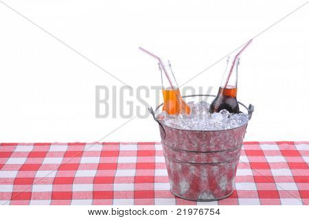 Two soda bottles in bucket of ice on checkered table cloth isolated on white