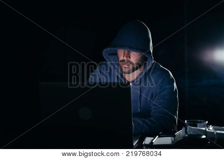 criminal mysterious man doing something illegal on a laptop, in the dark, a hacker