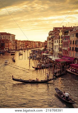 Gondolas floats along the Grand Canal at sunset in Venice, Italy. Grand Canal is one of the major water-traffic corridors in Venice.