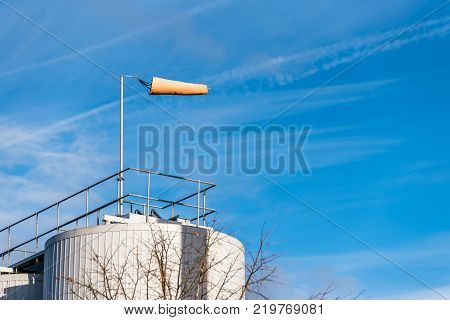 Air Wind Direction Indicator on Chemical Factory over Blue Sky air sock, drogue, wind sleeve, wind cone.