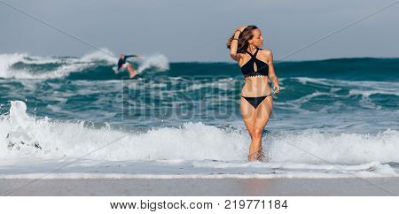Beautiful girl in black swimwear coming out of the ocean with surfer riding the wave in the background