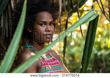 Melanesian pacific islander athlete girl with afro hair style in the jungle, half profile
