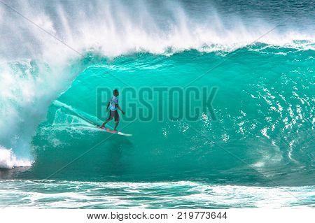 Surfer riding tube barrel section of big green wave at Padang Padang beach, Bali, Indonesia