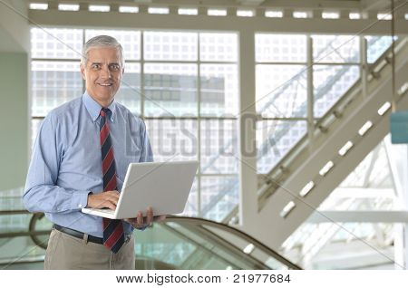 Businessman with White laptop computer in front of Escalator in modern office building