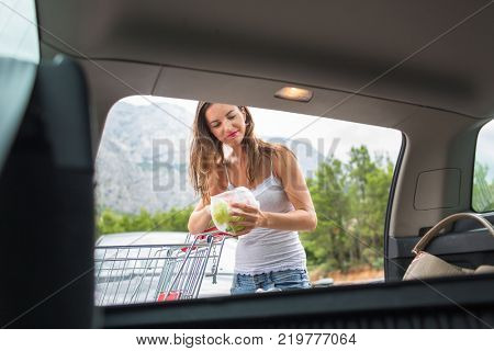 Beautiful young woman shopping in a grocery store/supermarket, putting the groceries she bought in her car (color toned image)