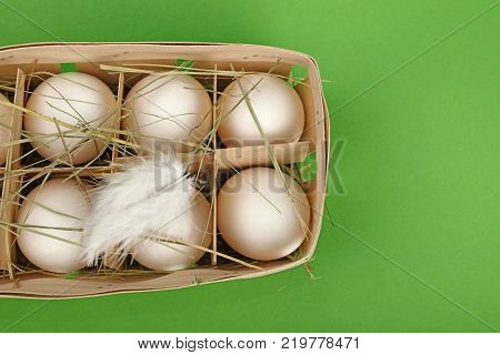 Six fresh white farm chicken eggs in wooden container box with hay and feather over green background elevated top view directly above