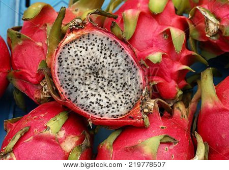 Close up several red ripe pitaya or white pitahaya dragon fruit with one cut cross section half on market stall high angle view