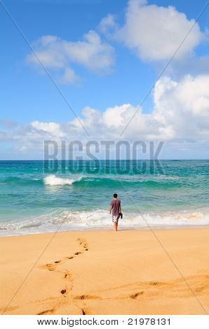 Teenage male walking into the surf on a tropical beach. Sunny day with bright blue sky and white fluffy clouds.
