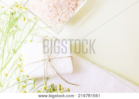 Spa resort background with bath essentials- a bowl of peach bath salt and a bar of homemade soap, camomile flowers and a terry towel on the table.Top view. Space for your text or product display.