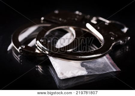 Handcuffs and cocaine on black background. Closeup