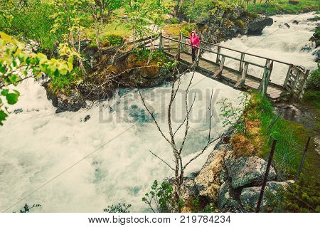 Travel and hiking. Tourist woman standing on bridge enjoying waterfall torrential river along the Aurlandsfjellet mountains in Norway Sogn og Fjordane foggy hazy summer day