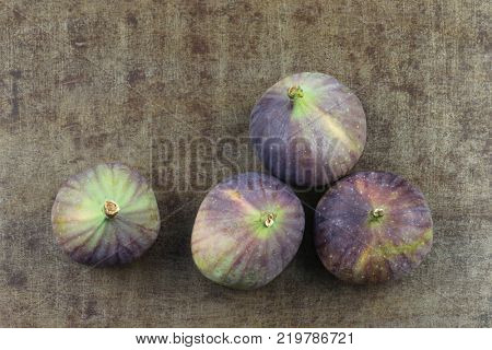 three figs (Ficus carica) on a grungy metal background