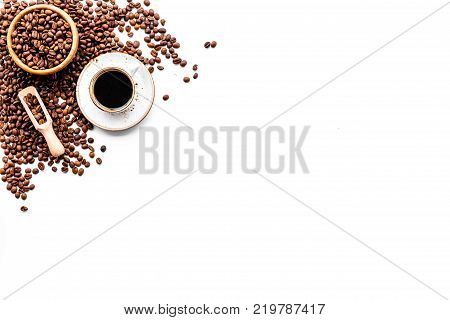 Coffee concept. Roasted beans and cup of espresso on white background top view.