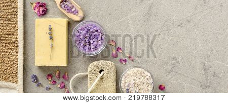 Bath and spa accessories with handmade Soap and sea salt on marble background . Lavender Spa treatment with dried lavender and rose petals