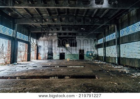 Ruined interiors of abandoned industrial hall. Charred walls.