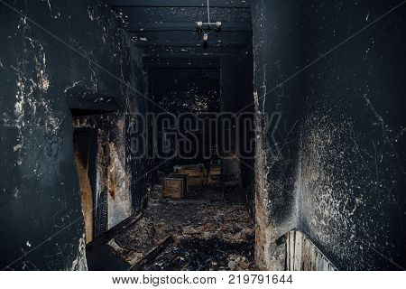 Burned room interior in apartment house. Burned furniture and charred walls in black soot.