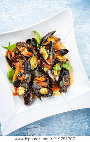 Traditional Italian blue mussel in white wine sauce as close up on a plate with copy space