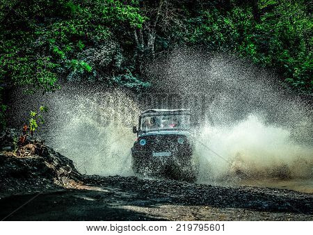 a trip on an off-road vehicle. off-road car at high speed crosses a mountain stream