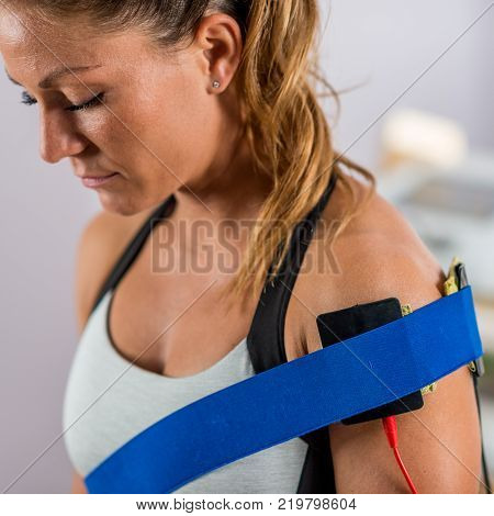 Electrical stimulation in physical therapy. Electrodes positioned at a patient's shoulder. Woman patient